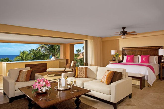 A view of a Romance Master Suite at Zoëtry Casa del Mar Los Cabos complete with a sitting area and a private balcony with an outdoor, infinity edge Jacuzzi.